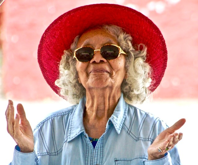older woman with open arms showing self-compassion